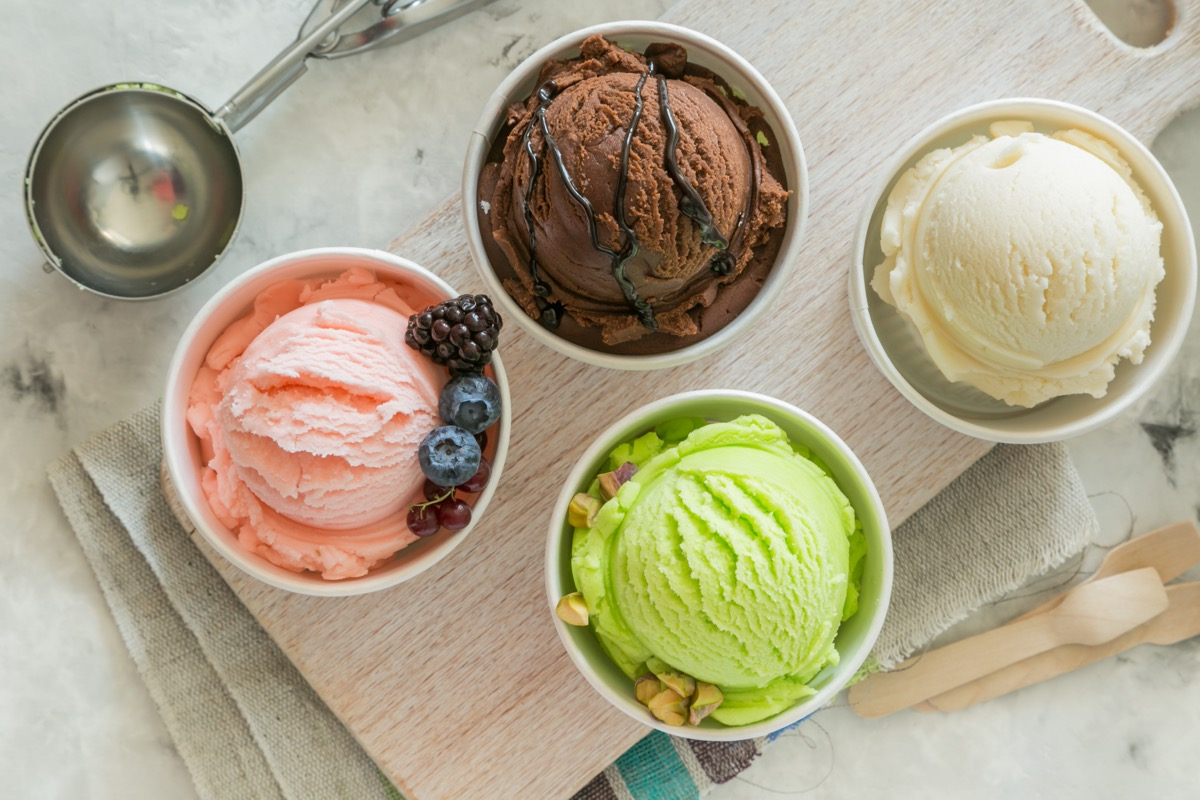 colorful ice cream in paper cups next to metal scoop