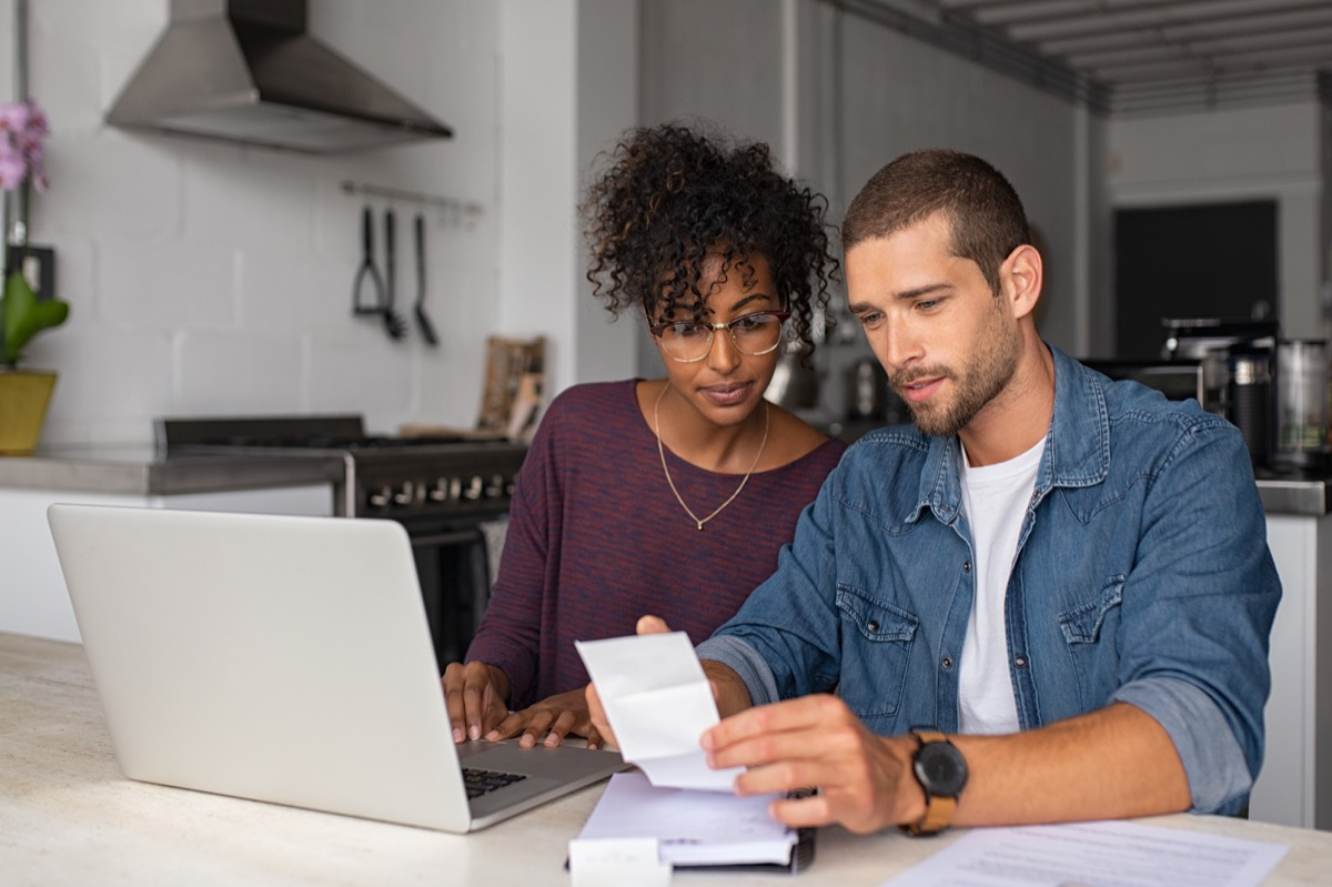 couple checking bills while managing accounts on home banking sitting at home discussing finance for the month