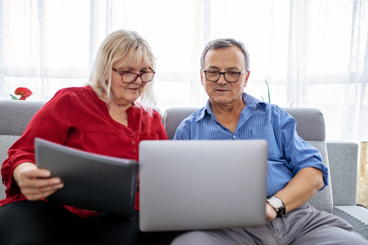 Senior, retired couple using a laptop, sitting on a couch together