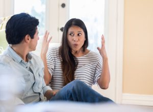 An animated mid adult woman throws up her hands in frustration as she speaks to her unrecognizable husband at home. They are sitting on their living room floor.