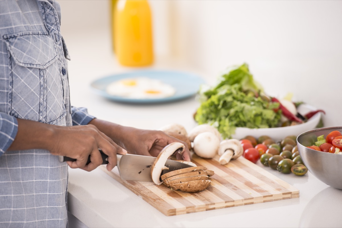 Unrecognized woman preparing fresh salad, chopping mushroom, cherry tomato, and lettuce.