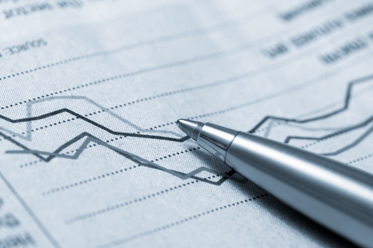 paper showing a graph indicating a decline in sales or profits with a silver pen on top