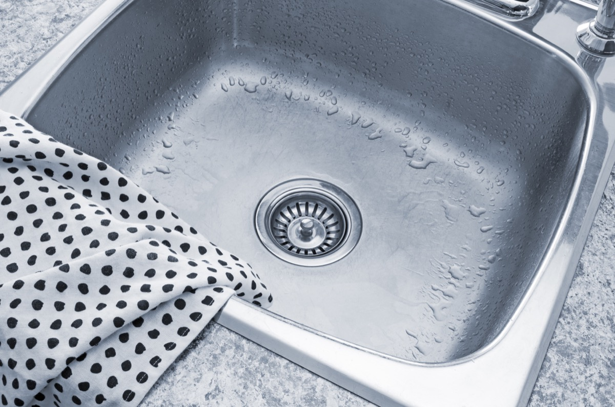 Clean metal sink and polka dot kitchen towel.