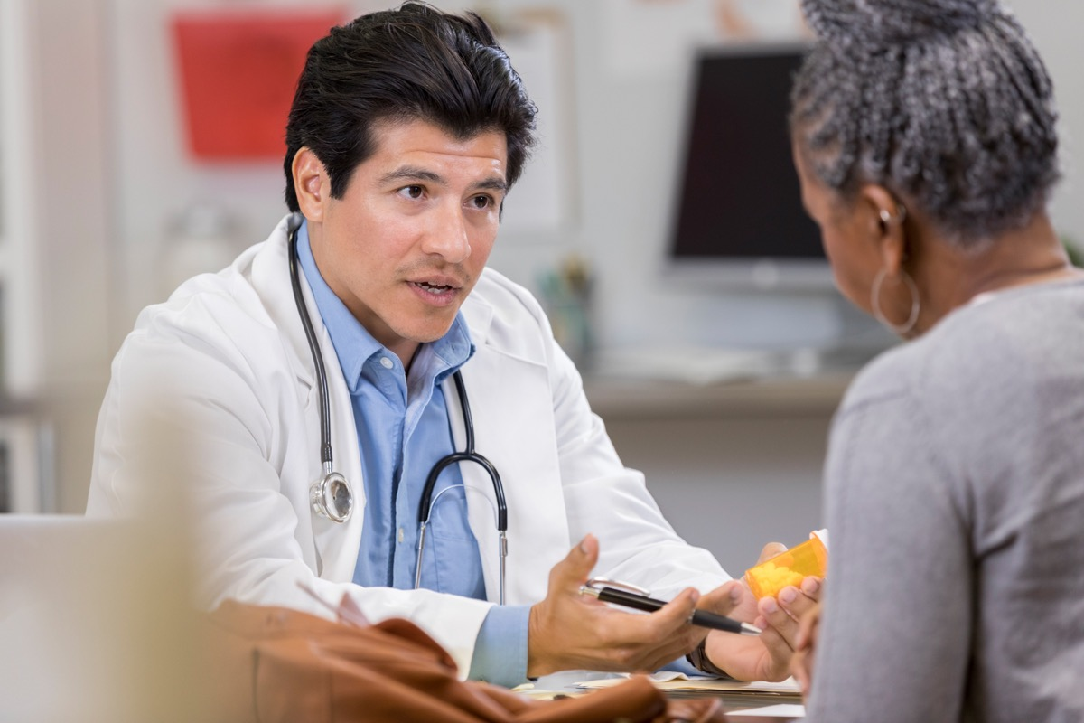 A confident male doctor sits across from an unrecognizable female patient and holds a medication. He gestures as he explains the new prescription.