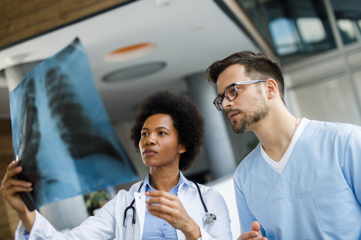 Medical experts cooperating while analyzing medical scan in the hospital