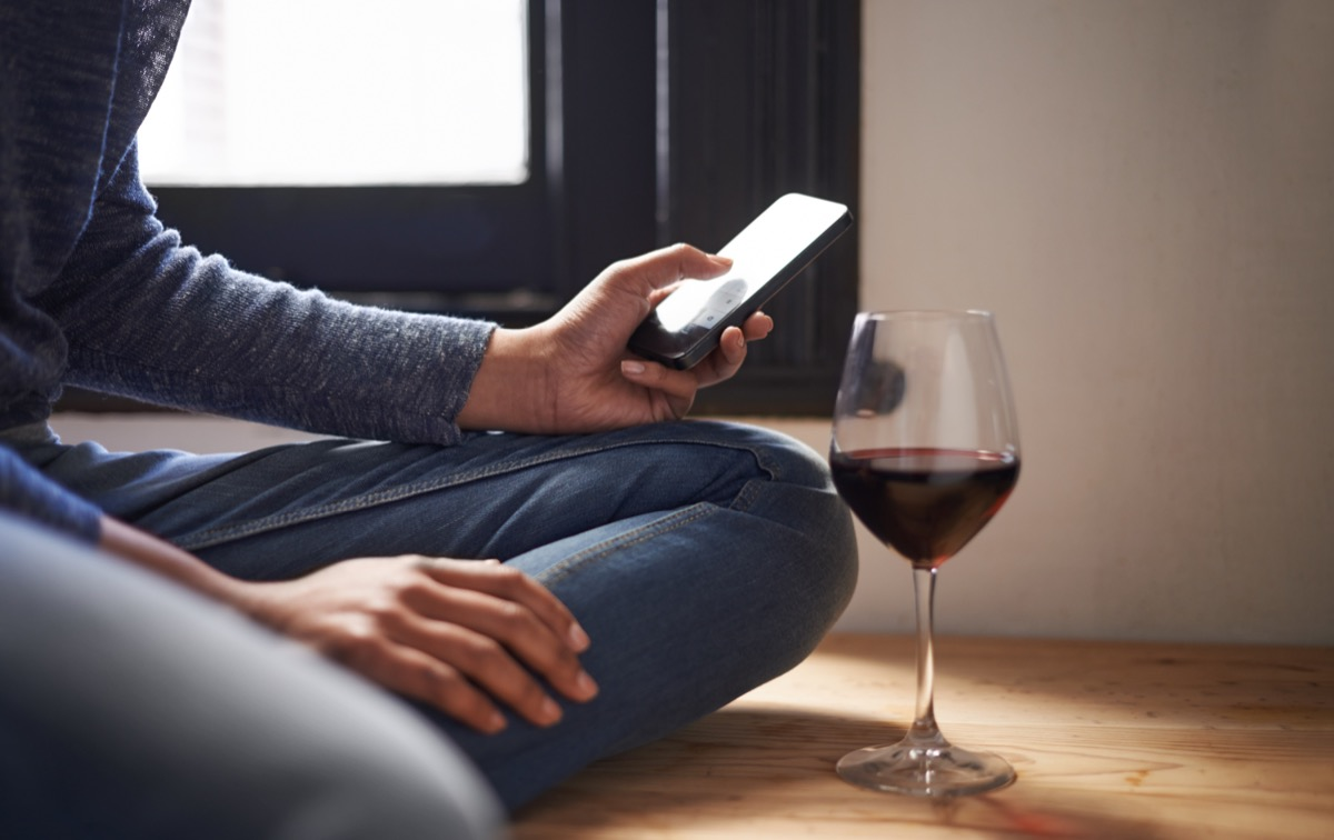 Cropped shot of a woman sending a text message with a glass of wine beside her