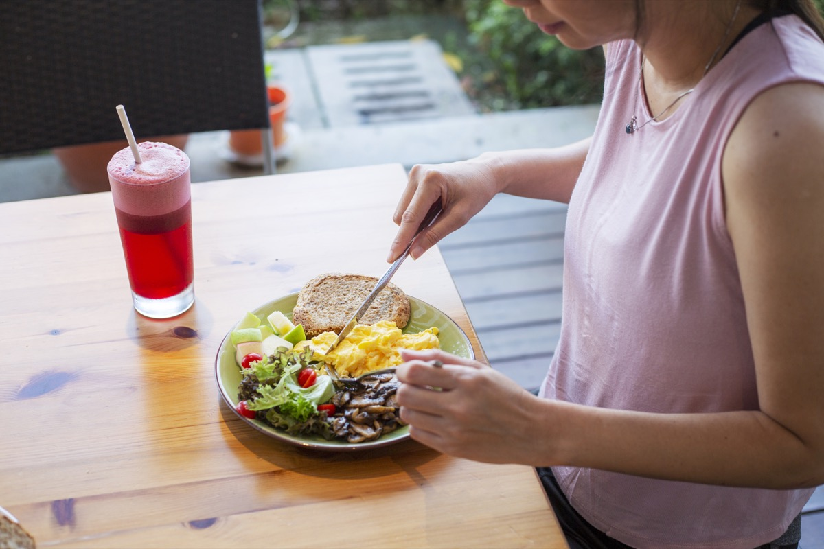 unrecognized woman eating healthy homemade breakfast with salad at backyard garden