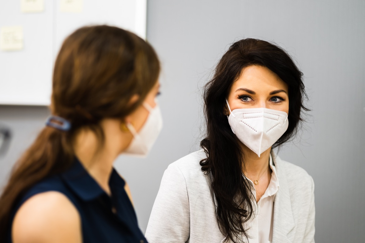 two women with facemasks on, looking eye to eye