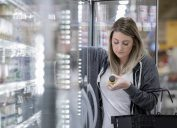 Young woman studies nutrition label of almond milk while shopping in grocery store