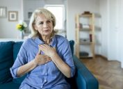 Senior Woman Suffering From Chest Pain While Sitting on Sofa at Home. Old Age, Health Problem, Vision and People Concept. Heart Attack Concept. Elderly Woman Suffering From Chest Pain Indoor