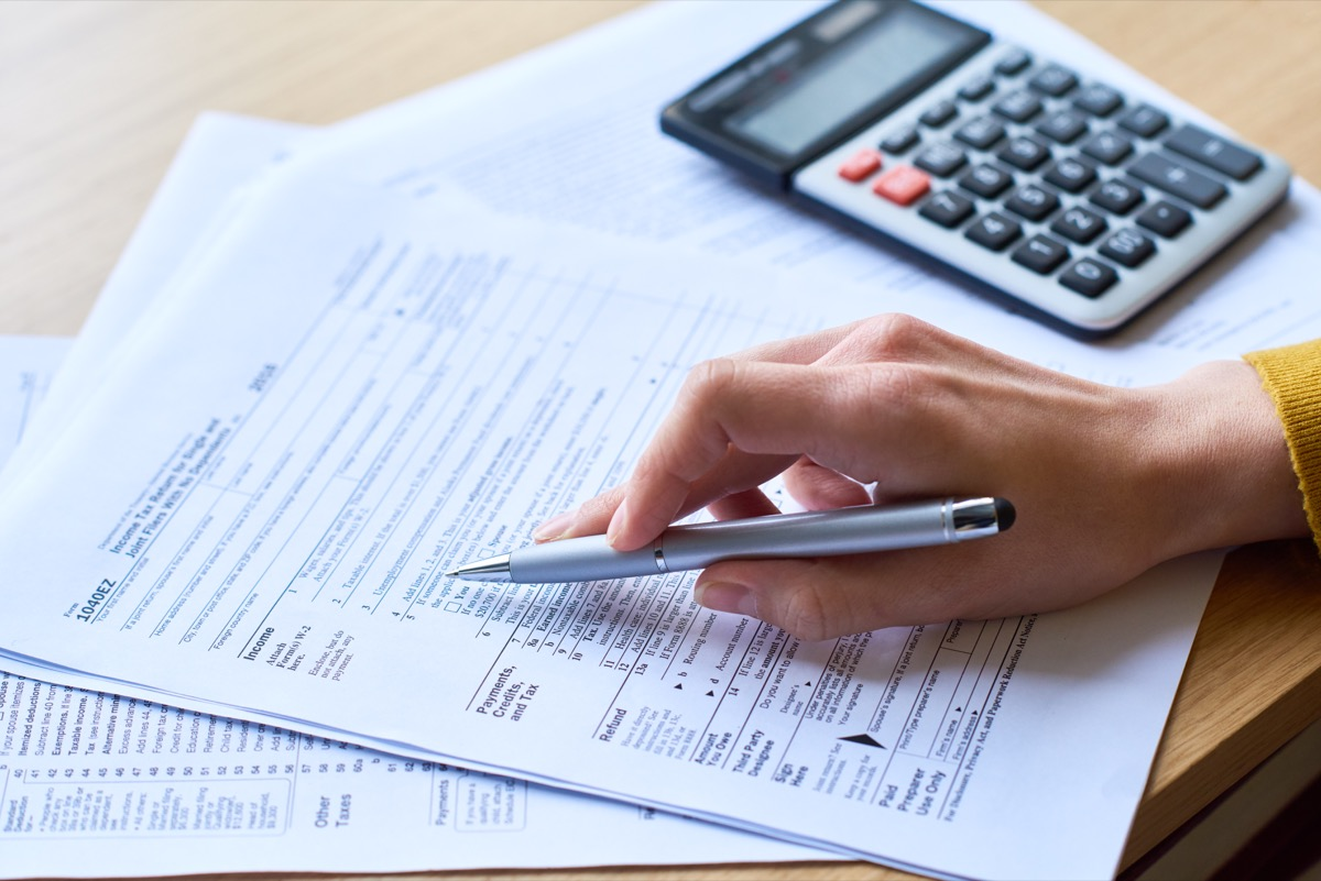 Close-up of unrecognizable woman working with tax return form: she checking papers and using calculator
