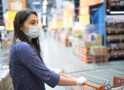 Woman with face mask, shopping for groceries in a supermarket during COVID-19 pandemic