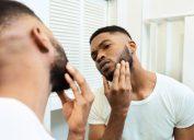 guy looking at his beard at bathroom mirror