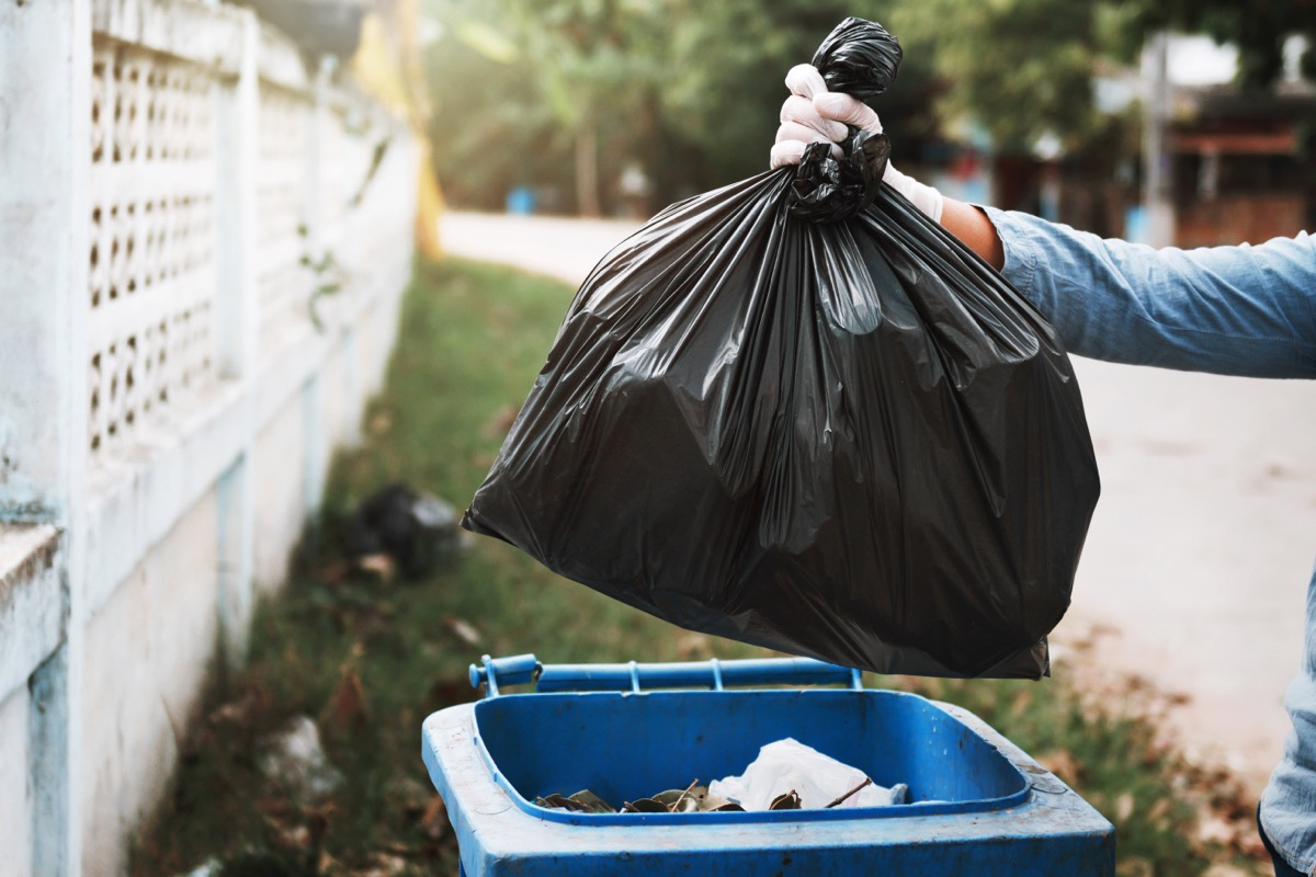 person putting black trash bag into large outdoor trash can
