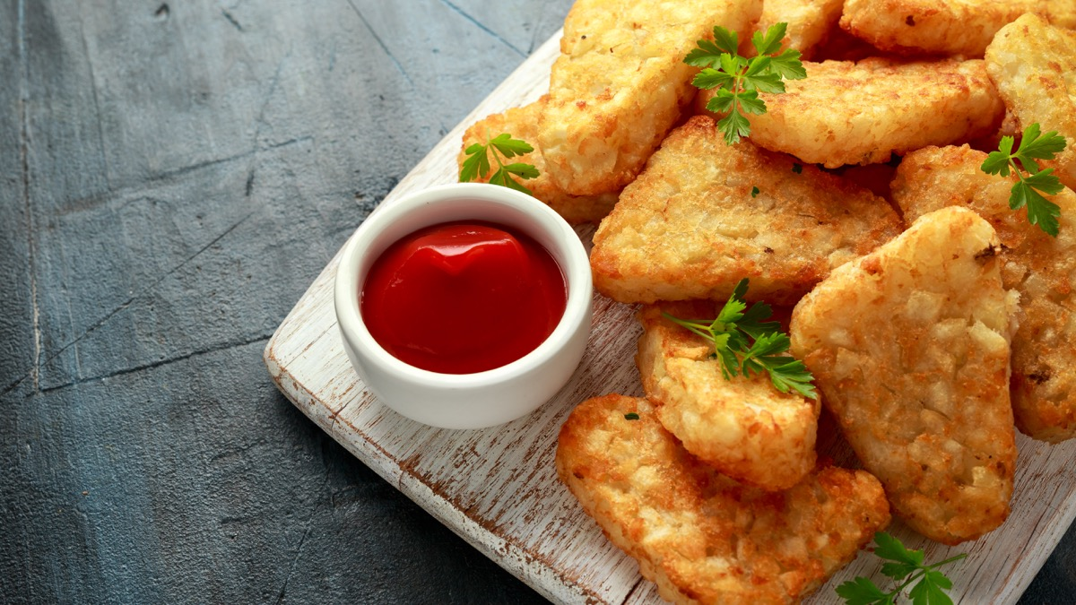 hash browns on wooden board, ketchup
