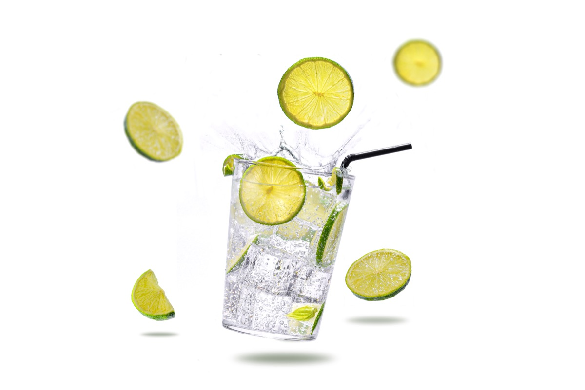 highball cocktail with lime, ice, glass, white background