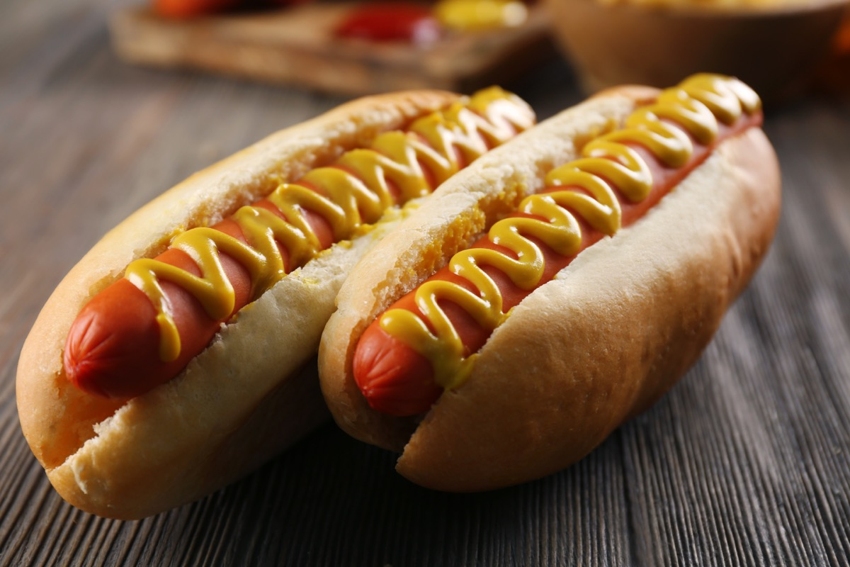 two hot dogs in a bun, with mustard, wooden table