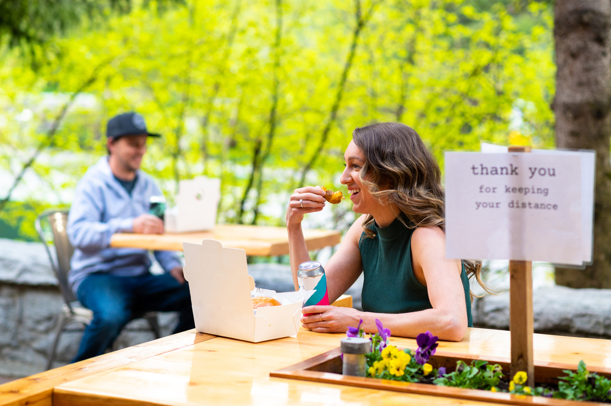 A young woman eating at a restaurant while socially distanced from other customers