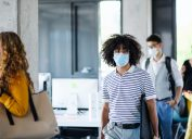 A group of young coworkers walk back into their office while wearing masks