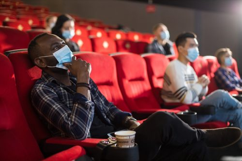 people sitting with masks inside a movie theater