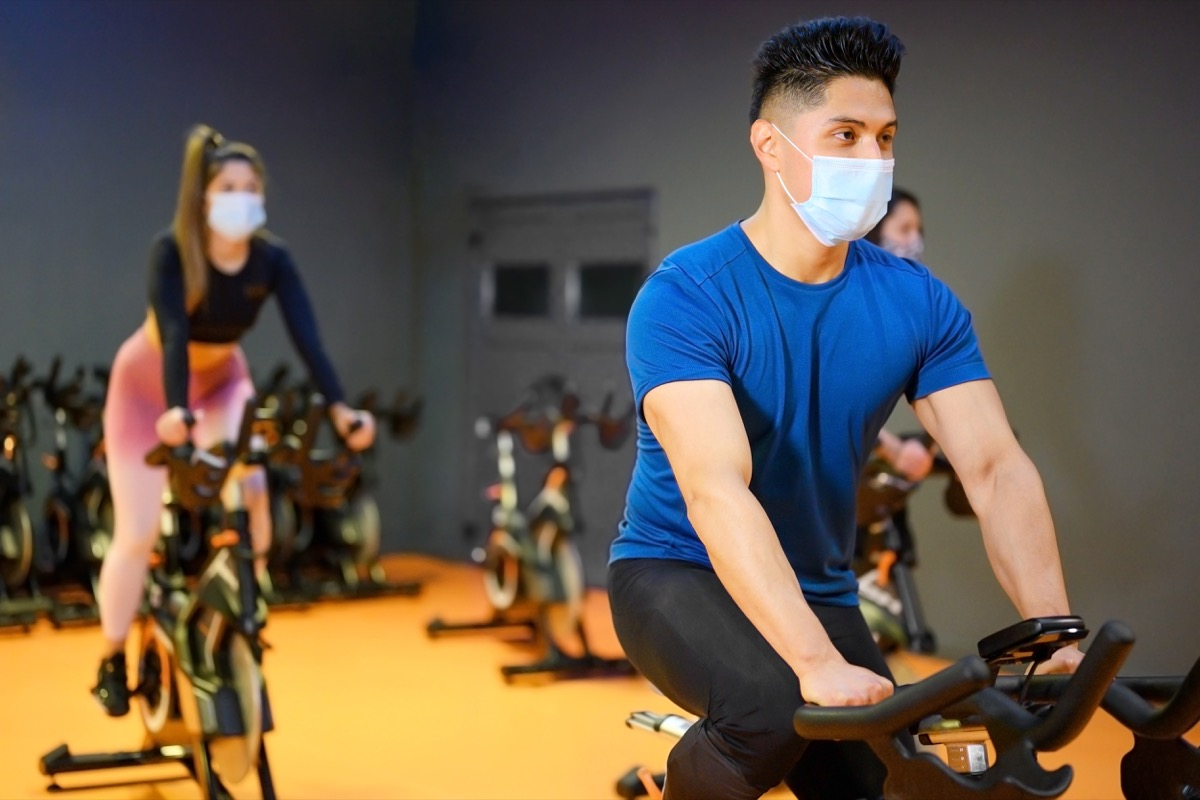 people cycling indoors during covid pandemic, wearing masks