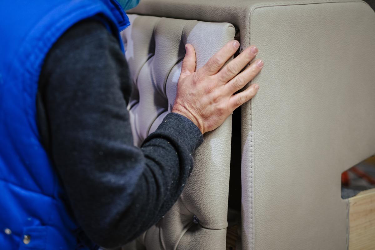 person in blue vest installing headboard