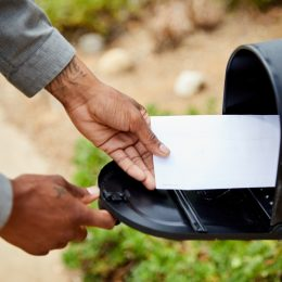 man standing outside of his house and removing an envelope from his mailbox