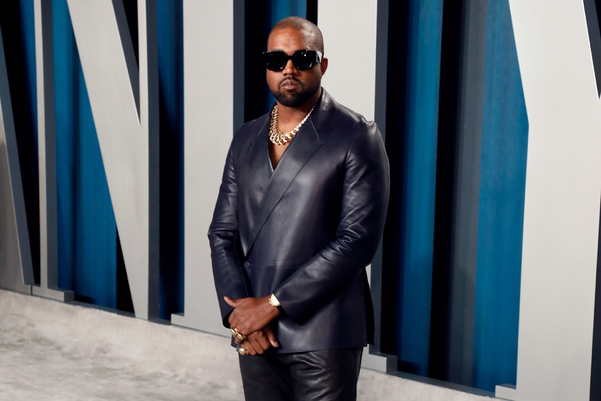 kanye west wearing a leather suit in front of vanity fair sign