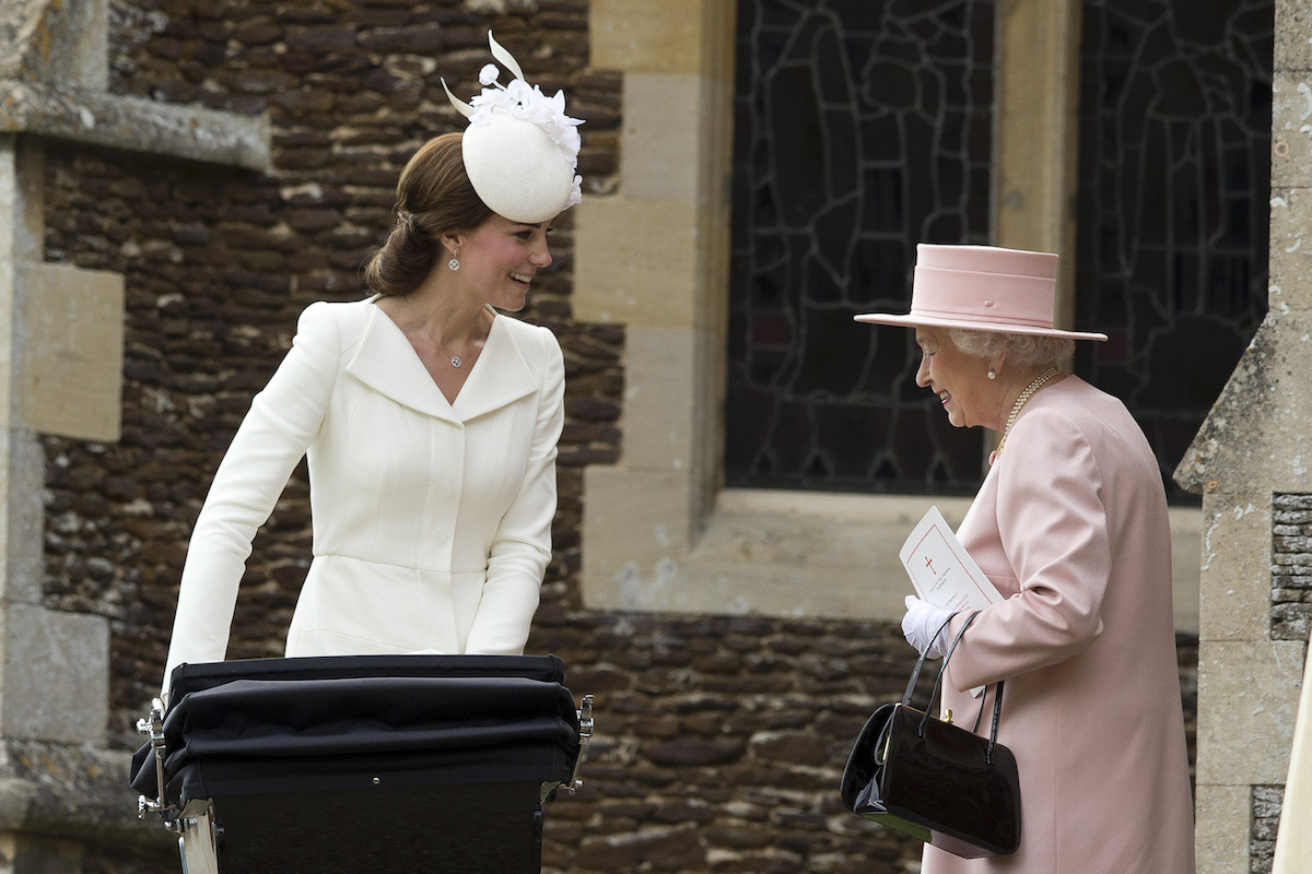 Queen Elizabeth II speaks to Catherine, Duchess of Cambridge, as she pushes in a pram Princess Charlotte of Cambridge at Church of St Mary Magdalene on the Sandringham Estate after the Christening of Princess Charlotte of Cambridge on July 5, 2015 in King's Lynn, England