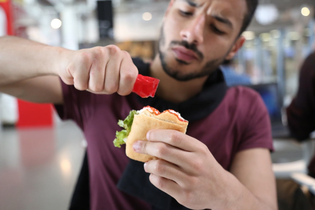 Hungry man sitting in a restaurant, holding a ketchup packet adding it to his sandwich