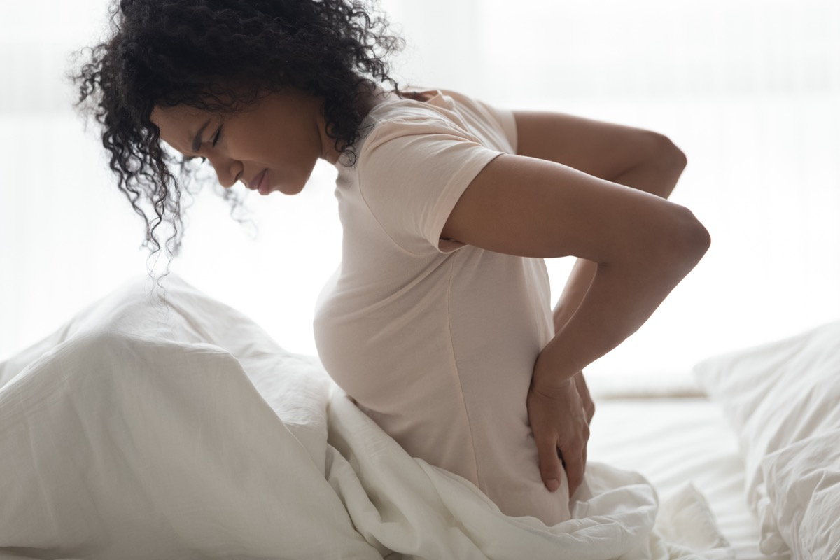 woman touching back feeling backache
