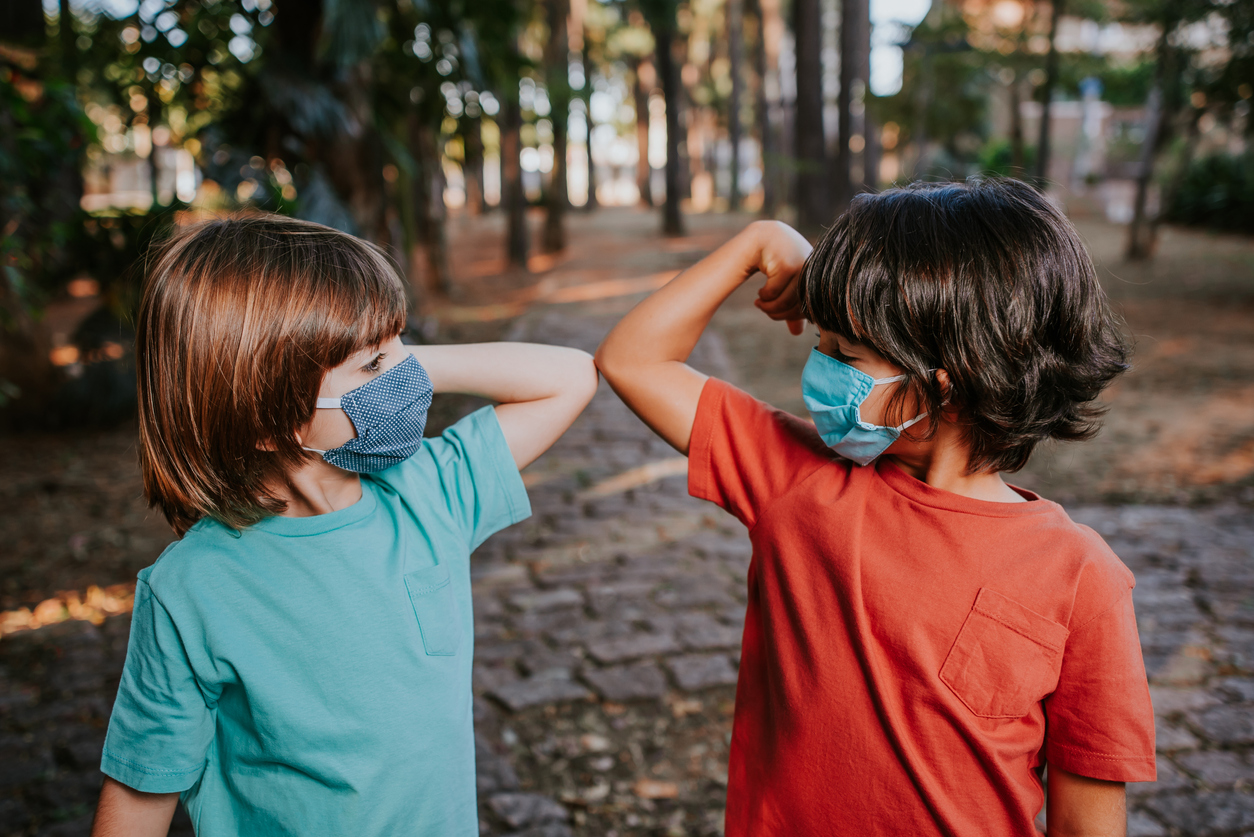 Two young boys wearing face masks bump elbows to say hello