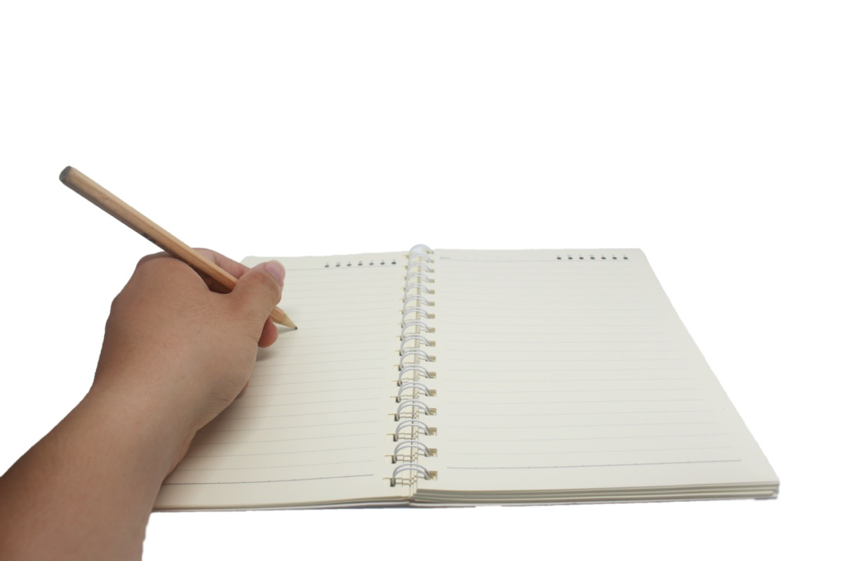 Left handed person writing in notebook