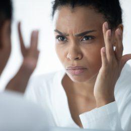Woman wearing white bathrobe looking in mirror at eyebrow hair
