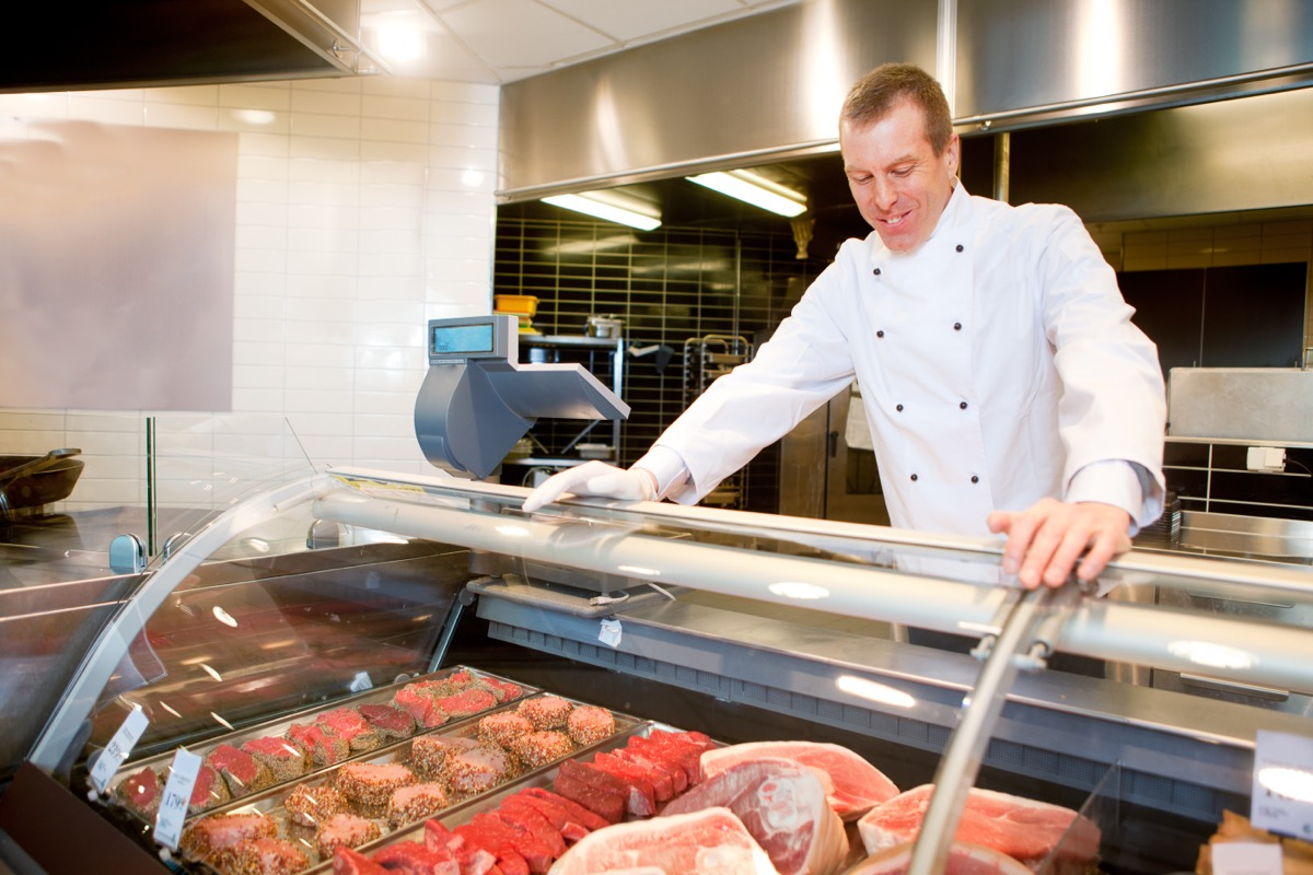 butcher behind meat counter