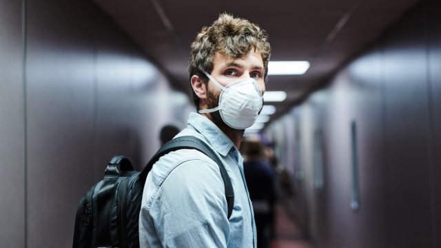 Shot of a young man wearing a mask while boarding a plane