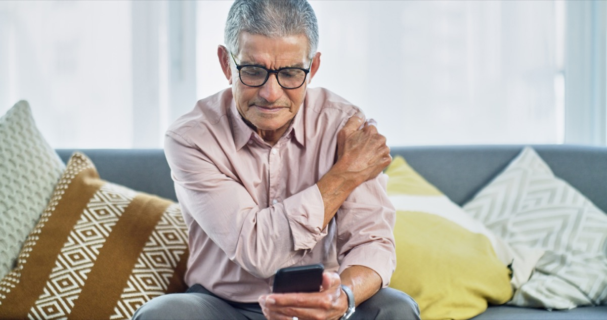 Shot of a senior man experiencing shoulder pain while using a smartphone at home