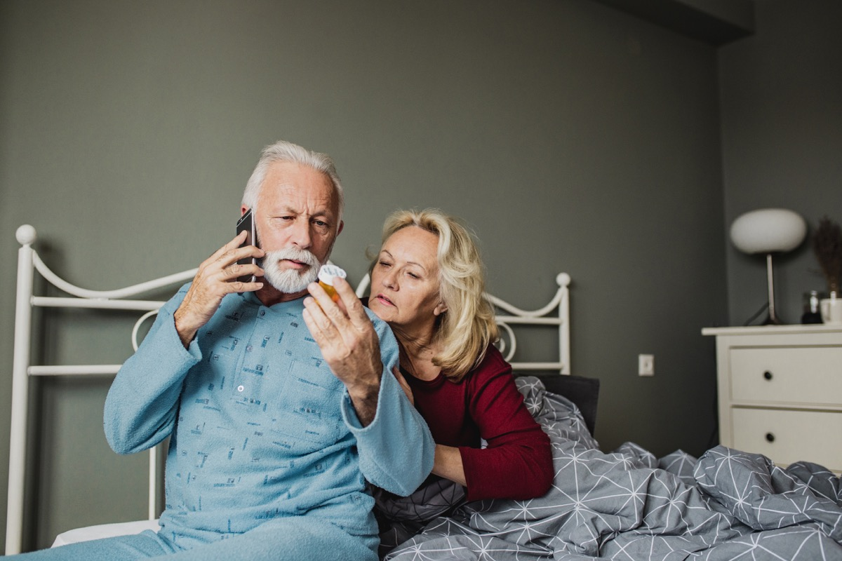 Senior couple is laying in bed, men is holding a medicine and calling a doctor