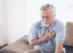 suffering from bad pain in his chest heart attack at home - senior heart disease
