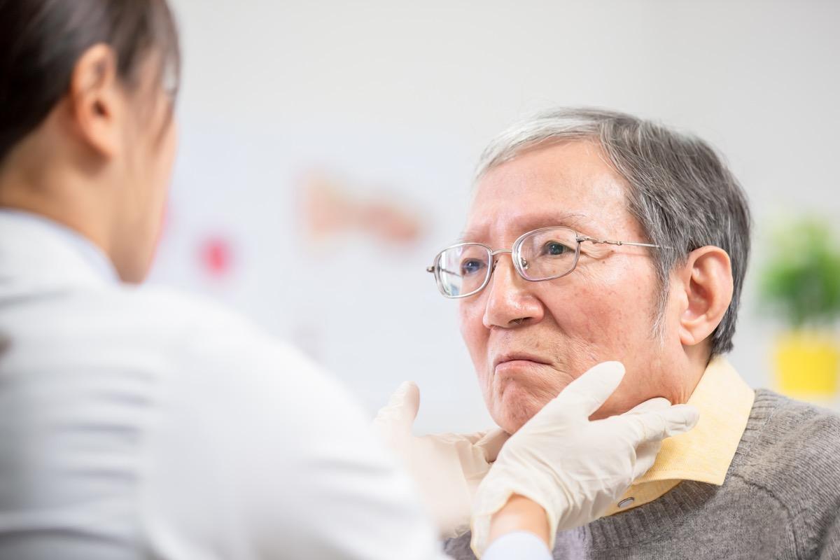Female doctor check throat for elder patient carefully