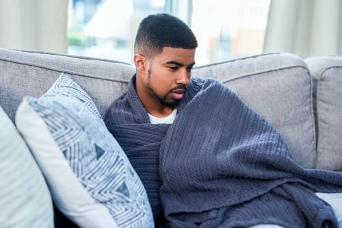 Shot of a young man feeling ill while sitting on a sofa at home