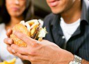 man eating burger while woman watches