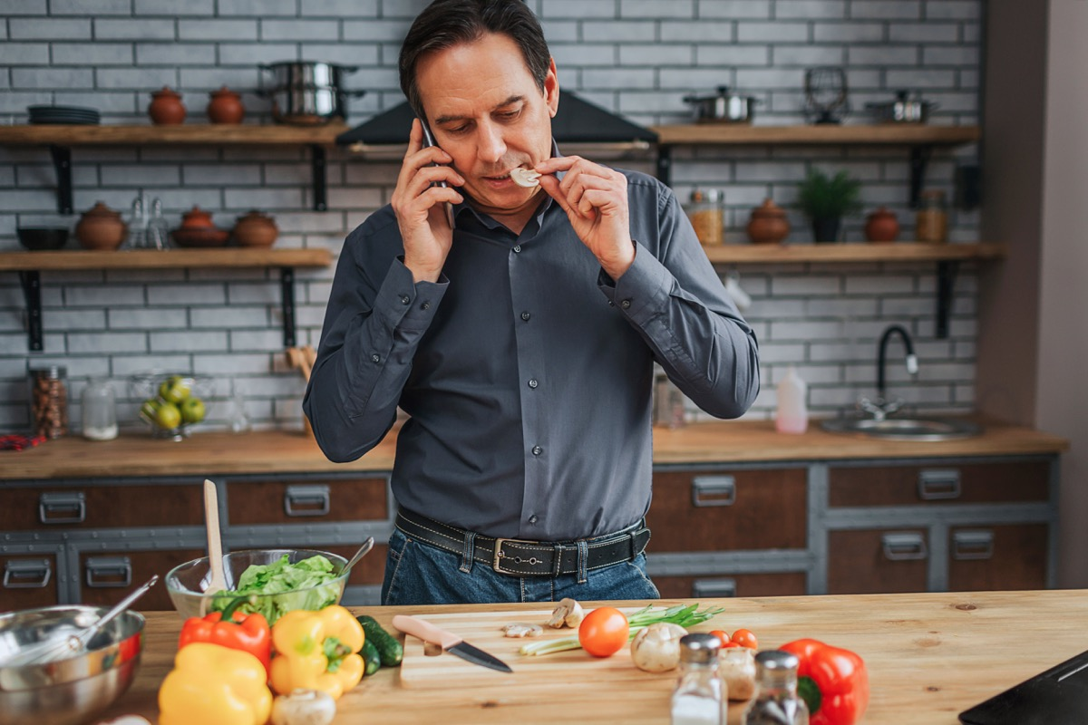 Adult man stand at kitchen table and talk on phone. He taste piece of mushroom. Man look down. Colorful vegetables lying on desk
