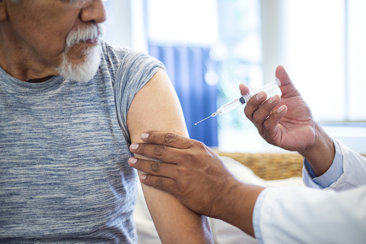 doctor injecting older man with vaccine