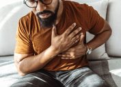 man holding his chest in pain indoors.