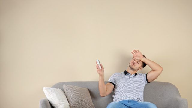 man sweating on couch holding air conditioner remote