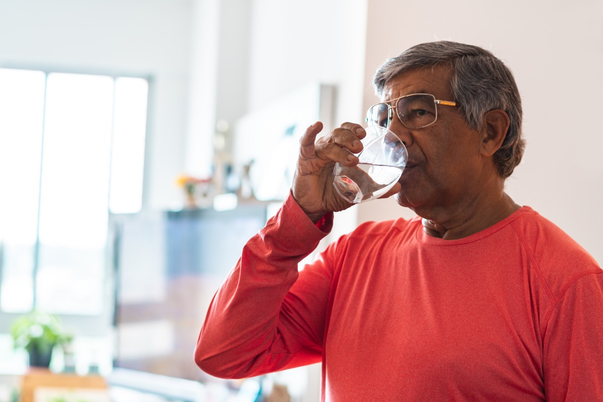 Senior man drinking water at home in the living room