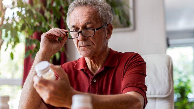 older man looking at supplements or medicine