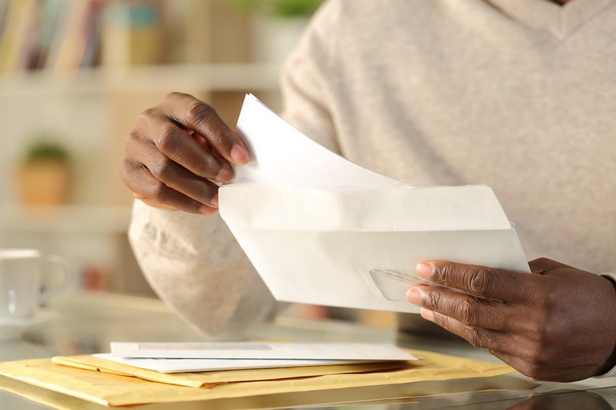 hands putting a letter inside an envelope