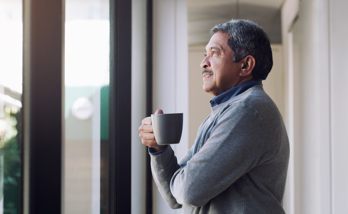 Shot of a senior man drinking coffee and looking thoughtfully out of a window
